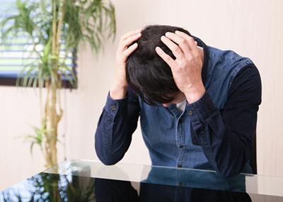 頭を抱える中年男性の画像